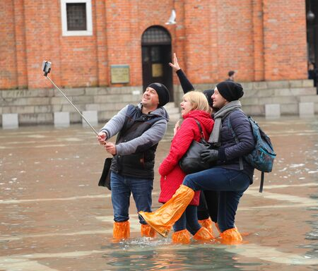 high tide: Venice, Italy - February 01, 2015: Tourists in San Marco square with high tide. Its a phenomenon which occurs in winter time. This can cause of a large inflow of water into the Venetian Lagoon.