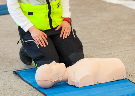 chest compression: Female instructor showing CPR on training doll.