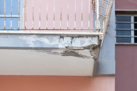 requiring: Balconies with cracked concrete and rusty irons requiring renovation. Stock Photo