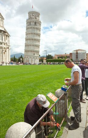 miracle square: Pisa, Italy - 14 May 2016: View of historical Pisa Tower in Cathedral Square with gardeners staring sign prohibiting to step on the grass. The tower is a well known landmark worldwide for its unintended tilt.