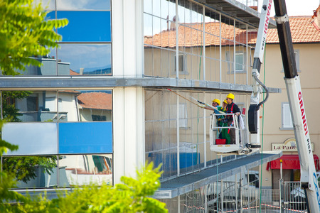 Empoli, Italy - 17 May 2016: Window cleaner working on a glass facade of the building. Cleaning Maintenance of USL 11 in Dei Cappuccini street in Empoli.
