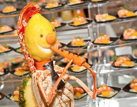 lavish: Decoration for buffet made with lobster, lemon and carrot. It is a person who plays the flute.