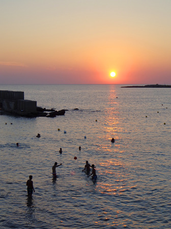 sun bathers: Tourists playing ball in the water in the sunset light