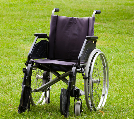 incapacitated: Empty wheelchair on grass field in the park. Stock Photo