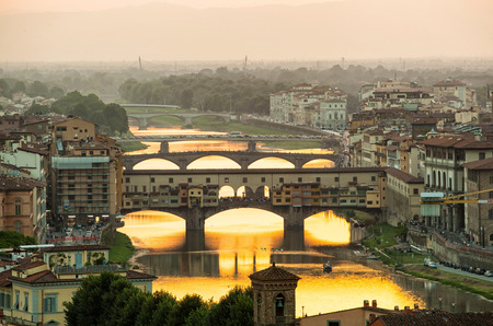 enlighten: Arno river and famous Ponte Vecchio enlighten by the warm sunlight. Florence, Italy.