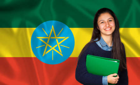 lessons: Teen student smiling over Ethiopia flag. Concept of lessons and learning of foreign languages. Stock Photo