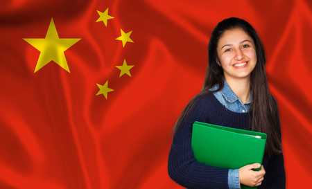 lessons: Teen student smiling over Chinese flag. Concept of lessons and learning of foreign languages.