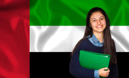 united arab emirate: Teen student smiling over United Arab Emirate flag. Concept of lessons and learning of foreign languages. Stock Photo