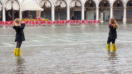 hardships: Venice, Italy - February 01, 2015: Tourists in San Marco square with high tide. Its a phenomenon which occurs in winter time. This can cause of a large inflow of water into the Venetian Lagoon.