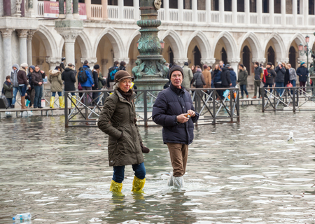 inflow: Venice, Italy - February 01, 2015: Tourists in San Marco square with high tide. Its a phenomenon which occurs in winter time. This can cause of a large inflow of water into the Venetian Lagoon.