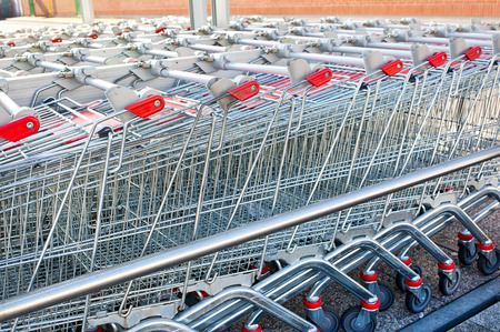 aluminum wheels: Rows of shopping carts at the entrance of supermarket Stock Photo