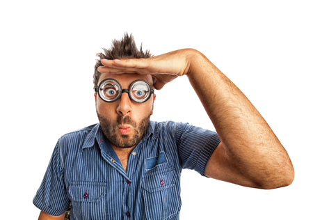 far away look: Man with funny expression and thick glasses looking far away on white background. Stock Photo