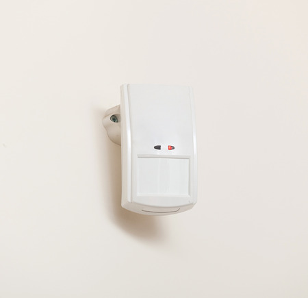 motion sensor: Motion sensor or detector for security system mounted on wall. Stock Photo