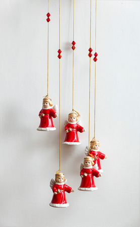 Still life of small pendants angels in Christmas clothes.