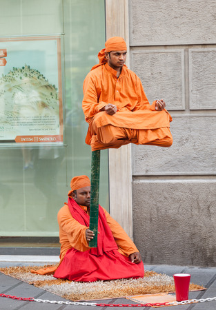 Naples, Italy - October 10, 2013: Street performer in clothing monk demonstrates trick of levitation show.