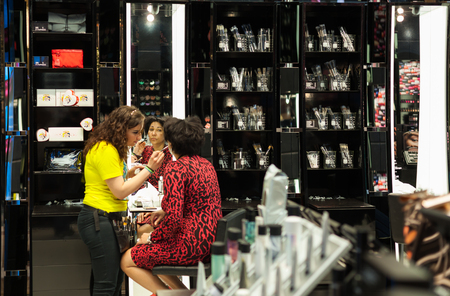 mack: Paris, France -  April 28, 2013: Try to make up a tourist in Mac Makeup shop on Champs Elysee. MAC Cosmetics was founded in Toronto, Ontario, Canada by Frank Toskan and Frank Angelo in 1984.