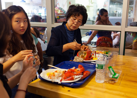 chelsea market: New York City, Usa - July 12, 2015: Asian tourists eating fresh lobsters in Chelsea Market. The market has a number of eateries and food outlets.
