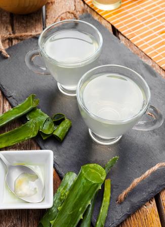 aloe barbadensis: Drink aloe vera and honey. Glass cups on a slate tray.