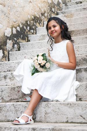 Glimlachend jong meisje in witte jurk voor eerste communie