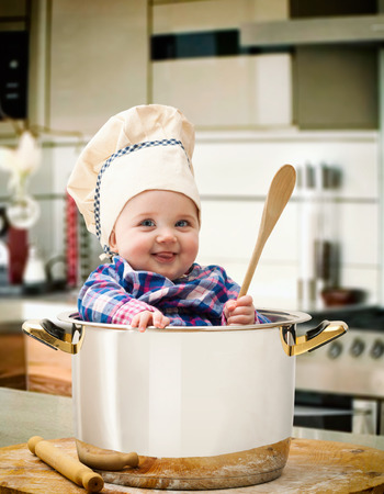 New Born baby girl Chef in a steel pot with wooden rolling pin and spoon. Banque d'images