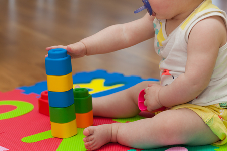 Toddler plays with building block on the colored rubber mat. Stock Photo
