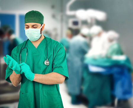 Surgeon wearing gloves in the operating room photo