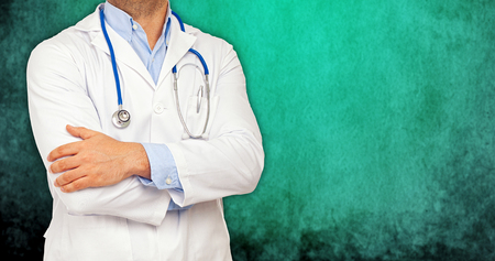 Half body of a doctor with crossed arms on green background. photo