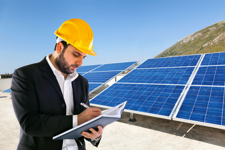Engineer with yellow helmet and big solar panels on background. photo