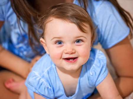 Portrait of a newborn baby girl smiling with two lower teeth. Stock Photo