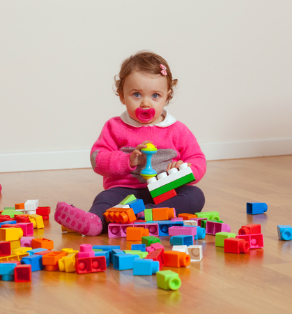 Toddler baby girl plays with soft rubber building blocks.
