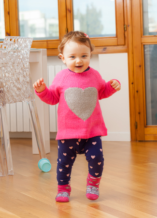 First steps of a female child at home on parquet floor.