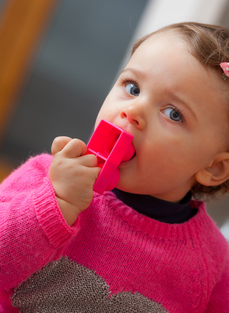 Toddler baby girl plays and puts in her mouth soft rubber building blocks.