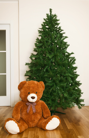 Bare artificial christmas tree in house with teddy bear.