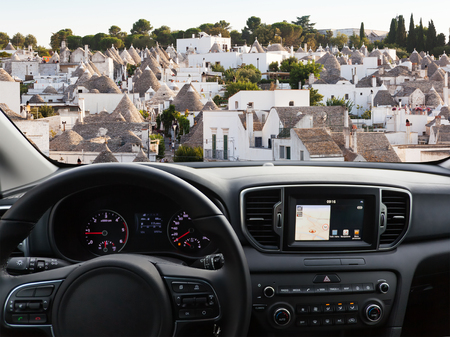 View of a car dashboard with a navigation unit traveling to Alberobello Stock Photo