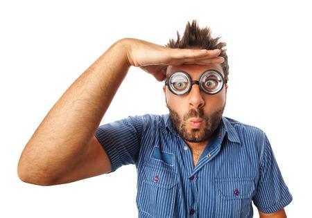 Mann mit lustigem Ausdruck und dicker Brille, die weit weg auf weißem Hintergrund schaut.