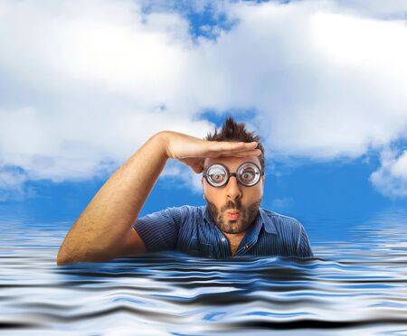 Man with funny expression and thick glasses looking far away in the water of the sea.