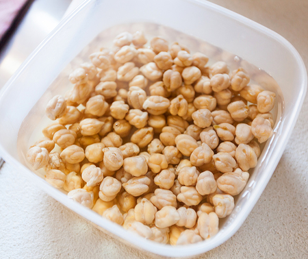 Chickpeas left in water to soak before cooking. Stock Photo