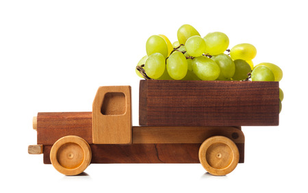 Wooden truck carries white grapes isolated on white background