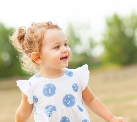 Pretty little girl with blond hair and blue eyes plays outdoor on a summer day.