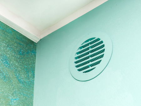 Circle vent window on green wall. Aeration system for plasterboard cavity. Stockfoto