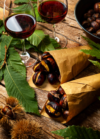 Roasted chestnuts in paper cones on wooden table. Stock Photo