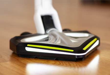 Vacuum cleaner with led light used on the floor in oak parquet.