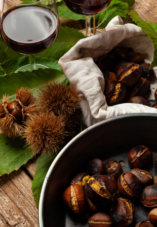 Roasted chestnuts in iron skillet on wooden table. Stock Photo