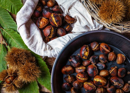 Top view of Roasted chestnuts in iron skillet on wooden table.