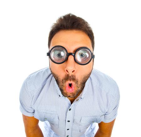 Młody człowiek z zaskoczonym wyrazem twarzy i grubymi okularami na białym tle.