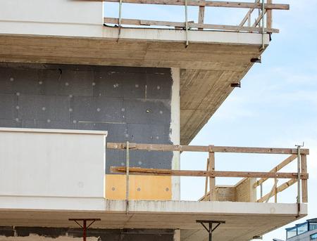 Obra de construcción: instalación de aislamiento térmico externo para la fachada del edificio. Foto de archivo