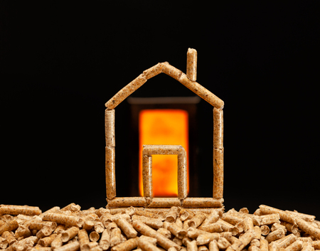 Miniaturhaus aus Holzpellets. Heizkonzept mit Brennkammer im Hintergrund. Standard-Bild