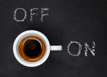 Top view of a Espresso Coffee in small white cup with a lettering ON and OF on black slate background Reklamní fotografie