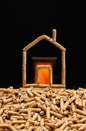 Maison miniature faite de granulés de bois. Concept de chauffage avec chambre de combustion en arrière-plan. Banque d'images