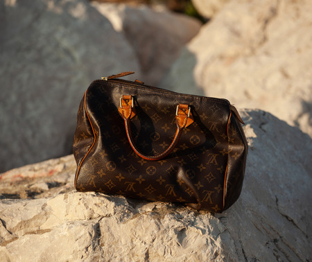 Formia, Italy - April 11, 2017: Louis Vuitton womens handbag on a rock in the sunlight. Publikacyjne